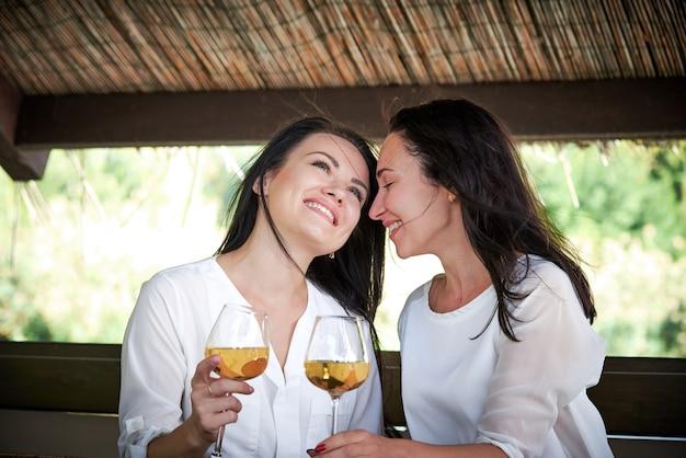 Duas meninas românticas que flertam no mandril no ar aberto.