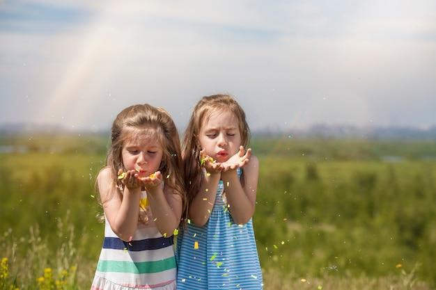 Duas meninas são lindas crianças na natureza soprando confetes ao sol