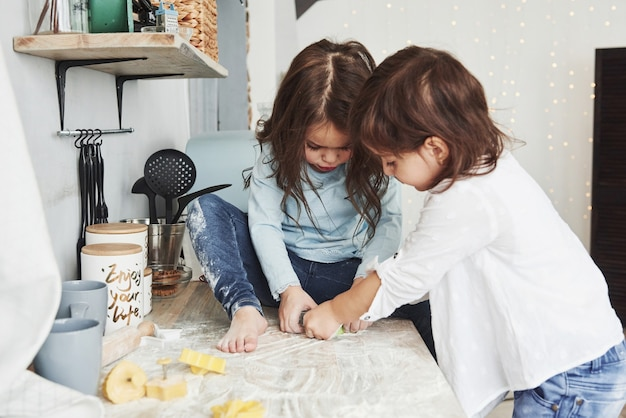 Duas meninas se divertindo. amigos da pré-escola aprendendo a cozinhar com farinha na cozinha branca.