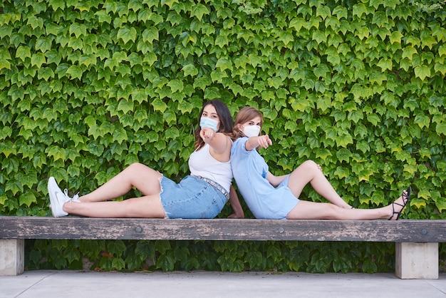 Duas meninas se inclinam de costas um para o outro, sentadas em um parque