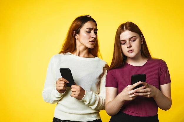 Duas meninas seguram telefones e uma garota olha no telefone de outra garota de pé