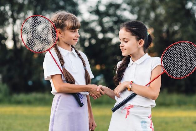 Duas meninas, segurando, badminton, apertar mão, com, um ao outro