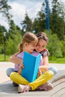 Duas meninas sentadas no banco ao ar livre lendo um livro