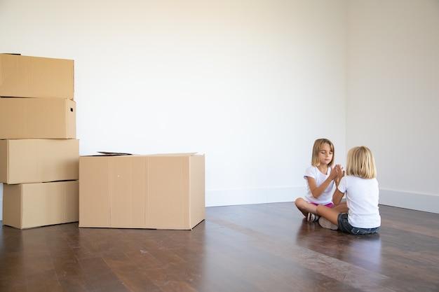 Duas meninas sentadas no chão perto de uma pilha de caixas em seu novo apartamento e brincando juntas