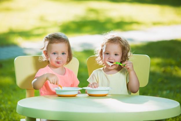 Duas meninas, sentado em uma mesa e comer juntos contra o gramado verde