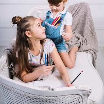 Duas meninas, sentar sofá, com, lápis, e, papel