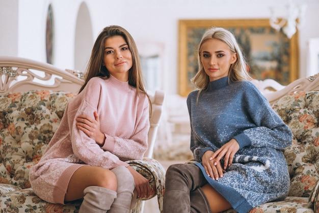 Duas meninas, sentar sofá, e, conversando