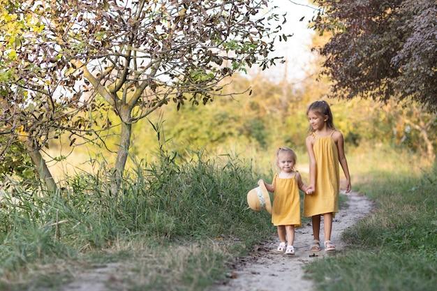 Duas meninas, sete anos e uma idade, ao ar livre