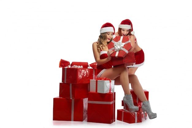 Duas meninas sexy de natal posando com uma pilha de presentes