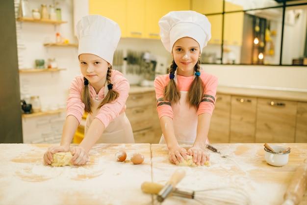 Duas meninas sorridentes cozinhando em bonés se divertindo