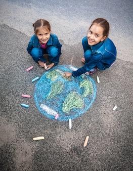 Duas meninas sorridentes desenhando a terra com giz na rua