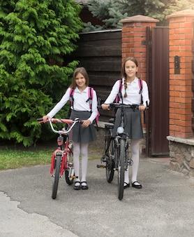 Duas meninas sorridentes em uniforme escolar com bicicletas na frente da casa