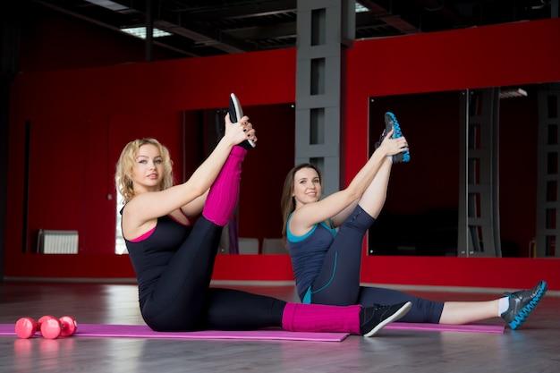 Duas meninas sorridentes fazem exercícios de alongamento em tapetes no centro de fitness