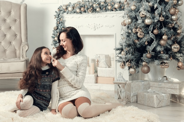 Duas meninas sorridentes, mãe e filha, localização no chão no quarto decorado de natal.