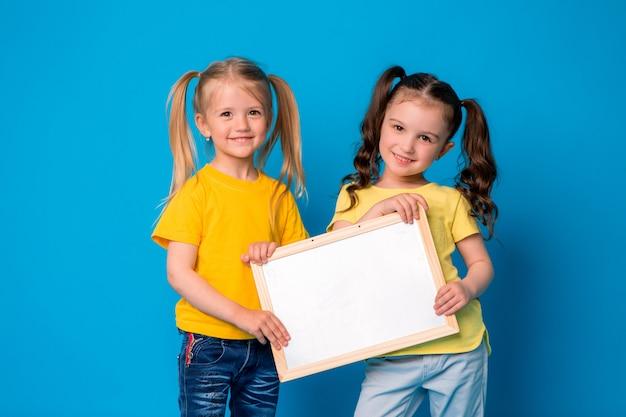 Duas meninas sorrindo com uma prancheta vazia sobre um fundo azul