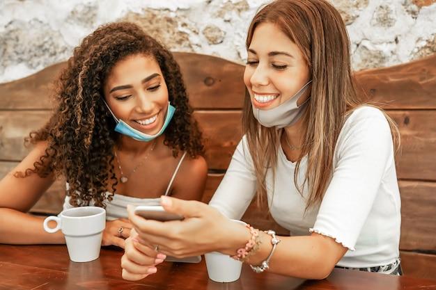 Duas meninas usando máscara de proteção, sentadas à mesa do bar, olhando para um smartphone com xícaras de café