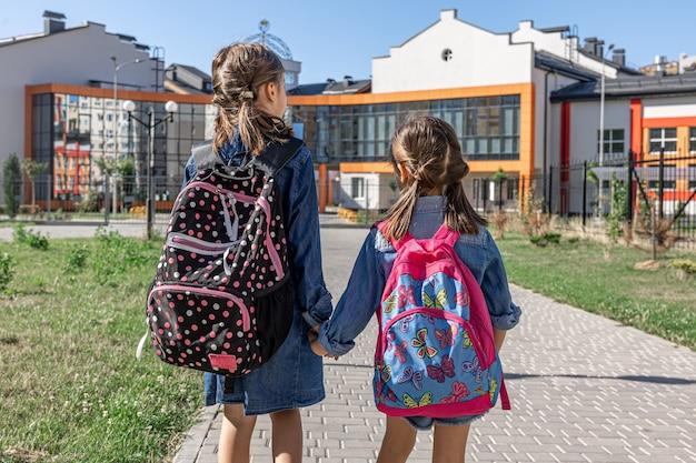 Duas meninas vão para a escola, de mãos dadas, vista traseira.