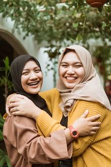 Duas meninas veladas riem e se abraçam quando se encontram