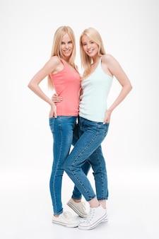 Duas meninas vestidas com camisetas e jeans posando. isolado sobre a parede branca. olhando para a frente.