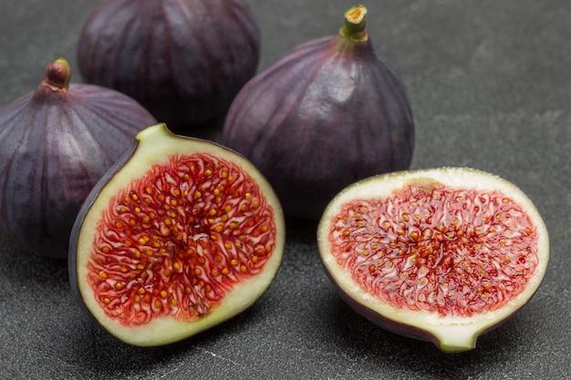 Duas metades da fig. três figos inteiros. fundo preto. vista do topo