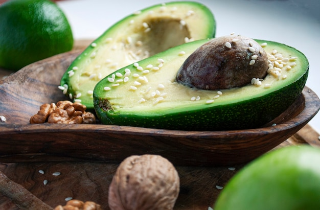 Duas metades de abacate em uma placa de madeira polvilhada com gergelim perto de nozes, maçã e limão.