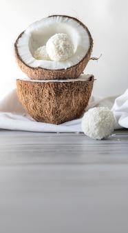 Duas metades de coco e doces de coco em uma mesa de madeira