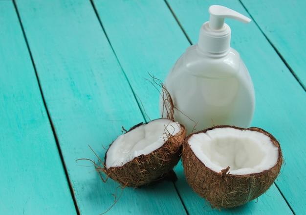 Duas metades de coco picado e uma garrafa branca de creme sobre fundo azul de madeira. conceito de moda criativa