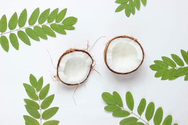 Duas metades de coco picado em fundo branco com folhas verdes