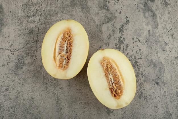 Duas metades de melão doce amarelo na superfície de mármore