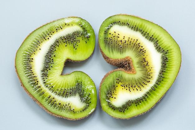 Duas metades de um kiwi feio em forma de coração em uma seção sobre uma superfície cinza.