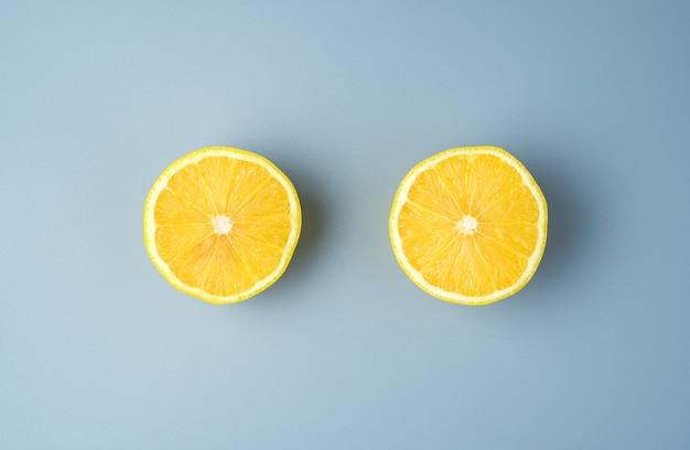 Duas metades de um limão suculento maduro em um fundo cinza.