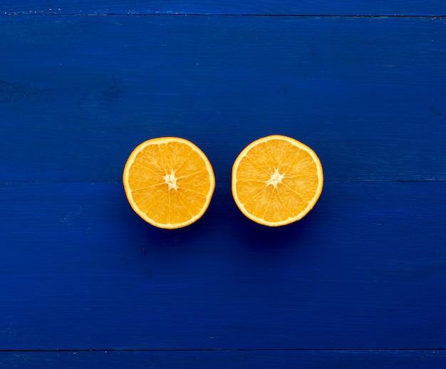 Duas metades de uma laranja redonda laranja sobre fundo azul escuro de tábuas pintadas na cor azul tendência