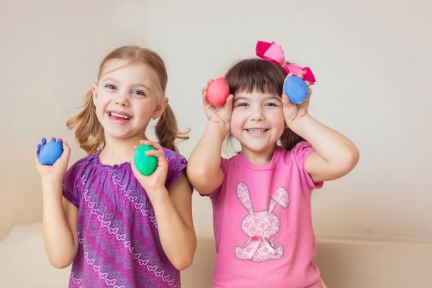 Duas miúdas giras felizes com ovos de páscoa nas mãos