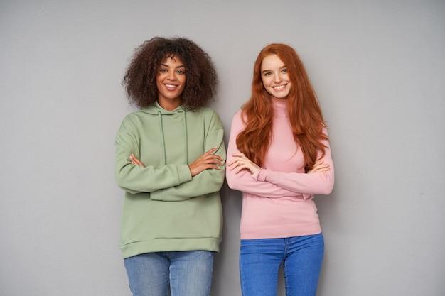 Duas moças atraentes e alegres, vestidas com roupas casuais, parecendo positivas e sorrindo amplamente, cruzando as mãos no peito enquanto posam sobre uma parede cinza