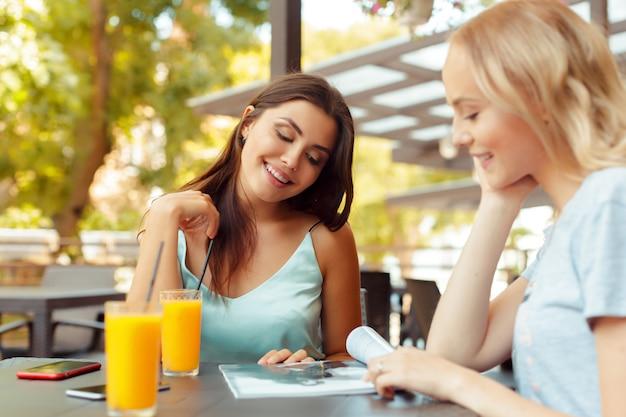 Duas moças bonitas que sentam-se pela tabela no café