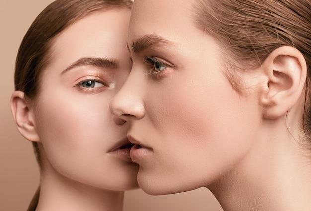 Duas moças sensuais bonitas com pele clara fresca do rosto jovem