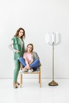 Duas modelos femininas, uma em pé da outra, sentam-se e olham fixamente para a frente em uma sala com interior