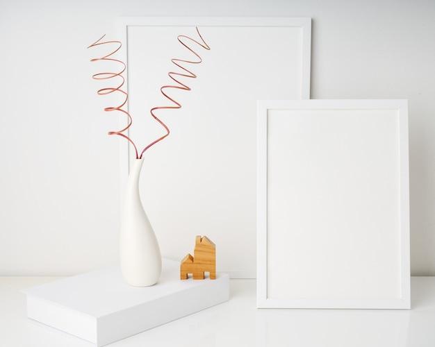 Duas molduras de pôster simuladas brancas com twings secos em um vaso branco moderno no livro branco e um modelo de casa sobre o fundo da parede da mesa branca