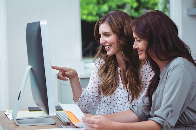 Duas mulher bonita usando o computador