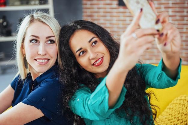 Duas mulher jovem e bonita fazendo selfie em um café, garotas de melhores amigas juntas se divertindo, posando de pessoas estilo de vida emocional