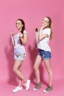 Duas mulheres adoráveis felizes ouvindo música em telefones celulares.