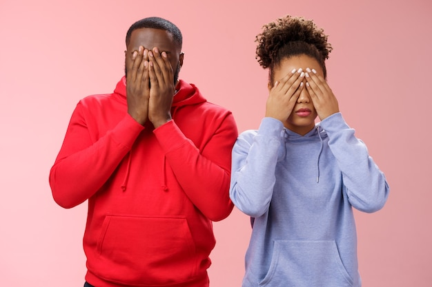 Duas mulheres afro-americanas em pé fundo rosa esconder rostos fechar olhos palmas cansadas procurando mentiras chateadas esperando sinal de comando ver, brincando de esconde-esconde, relutante local problemas pessoais
