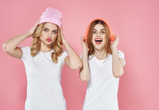Duas mulheres alegres chapéu rosa roupas da moda tendência estilo de vida isolado fundo