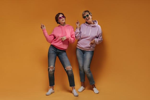 Duas mulheres alegres com penteado curto em óculos de sol legais com capuz elegantes e jeans skinny dançando em fundo laranja isolado.