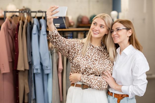 Duas mulheres alegres em trajes casuais elegantes fazendo selfie em ambiente boutique entre prateleiras com nova coleção de moda