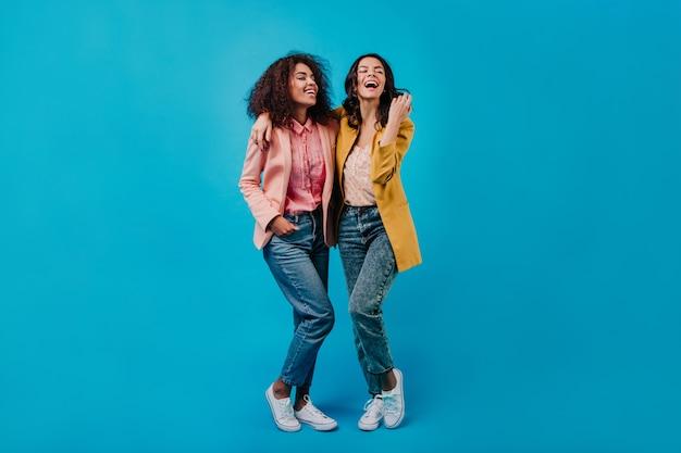 Duas mulheres alegres posando na parede azul do estúdio