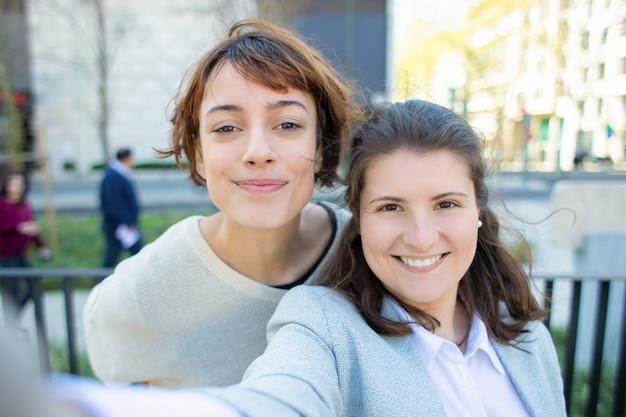 Duas mulheres alegres posando para auto-retrato