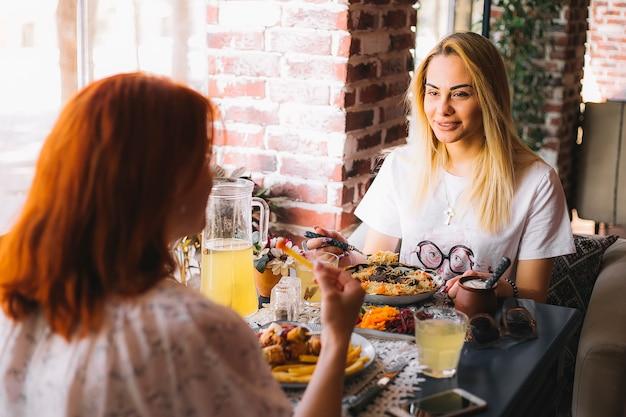 Duas mulheres almoçando no restaurante