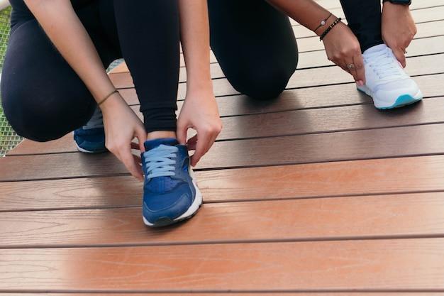 Duas mulheres amarra o cadarço e se prepara para correr