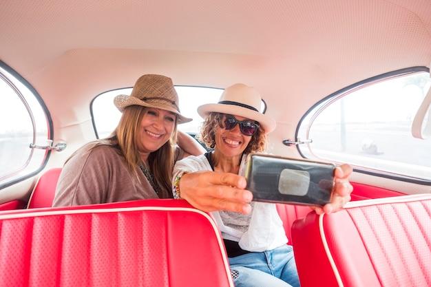 Duas mulheres amigas brancas curtindo um carro vintage vermelho tirando uma selfie com um smartphone moderno